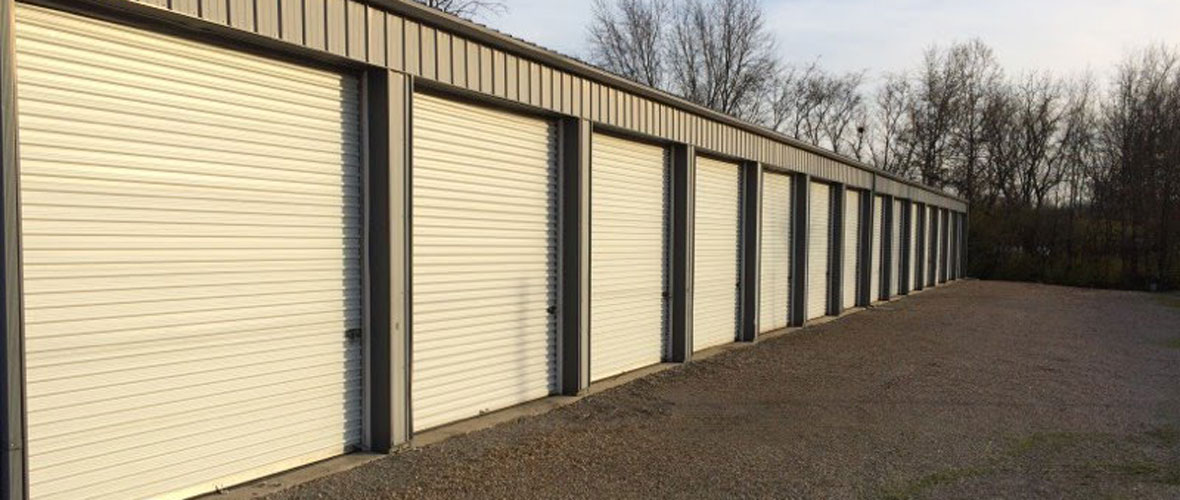 A building with rows of storage unit garage doors